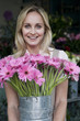 Woman florist or gardener holding a large pot of pink asters