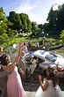 Usher, bridesmaid and flower girl (10-12) throwing confetti on bride and groom getting in car, smiling, elevated view