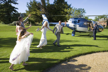 Bridesmaid, usher and flower girl (10-12) waving at senior bride and groom by helicopter