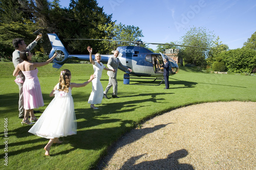 Usher, bridesmaid and flower girl (10-12) waving at senior bride and groom preparing to board helicopter