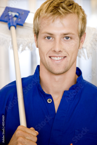 Office janitor or cleaning man with a broom or mop