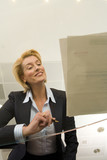 Businesswoman preparing to sign paperwork on glass table, smiling, low angle view through glass