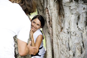Couple playing hide and seek through a hollow tree