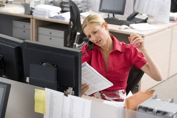 Young businesswoman looking at paperwork at desk in office, using telephone and stress ball, elevated view