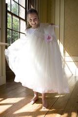Girl (10-12) holding up flower girl dress, smiling, portrait