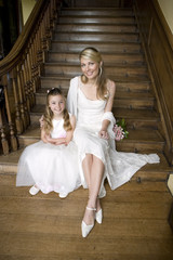 Bride sitting with flower girl (10-12) on staircase, smiling, portrait