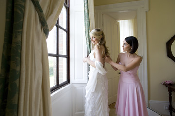 Bridesmaid adjusting bride's dress, smiling, side view