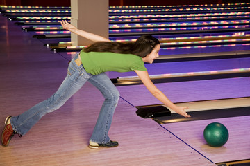 Teenage girl in bowling alley, rolling the ball