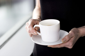 Hands holding a cup of coffee or tea