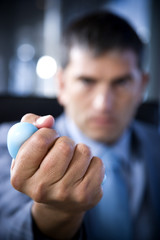 Close up of a businessman's hand squeezing a stress toy