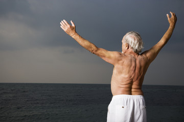 Portrait of a senior man looking out to sea with his arms outstretched