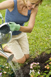 woman watering nee plants in flowerbed