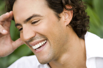 Portrait of a smiling man in a tropical garden.