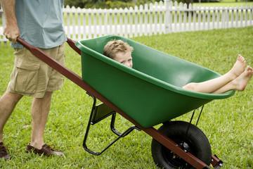 boy having a ride in a wheelbarrow