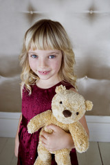 Young girl in party dress, holding a teddy bear