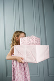 little girl carrying pile presents face obscured