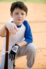 Boy with baseball bat kneeling on ground