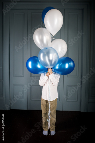 boy hiding behind a bunch of balloons
