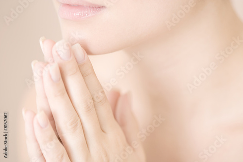 Young woman with hands together, praying or meditating