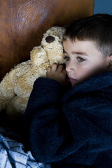 little boy snuggling up with teddy bear