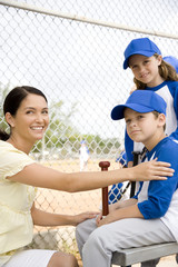 Mother congratulating son at little league baseball game