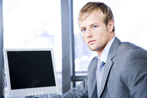 Businessman next to a computer screen on a modern office
