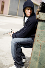 Portrait of a young man holding a gun sheltering behind a bin