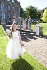 Flower girl on grass, wedding party in background, smiling, portrait