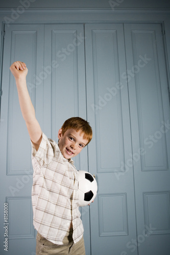 little boy stretching arm up in victory