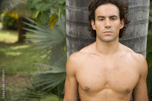 Portrait of a toned muscular man standing in a garden