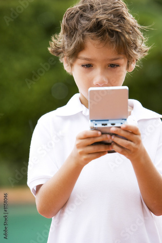 little boy playing with hand held computer game