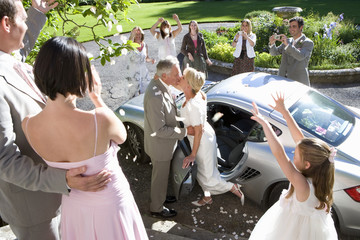 60's couple celebrating marriage next to car surrounded by family throwing petals.