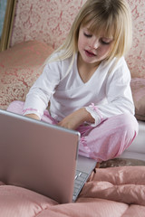 Young girl using a laptop computer in her bedroom