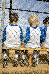 rear view little league baseball team sitting on bench
