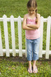 little girl standing against fence with arms folded