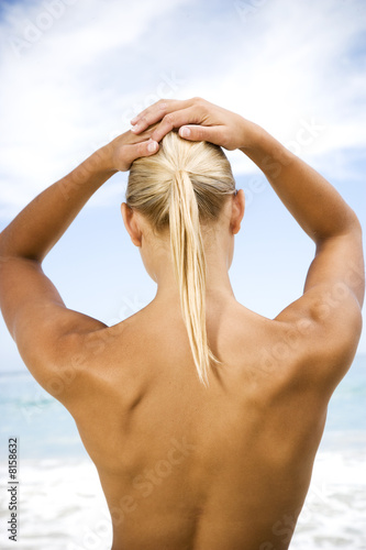 Rear view nude woman standing on the beach