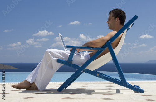 A man sitting on a deck chair using a laptop