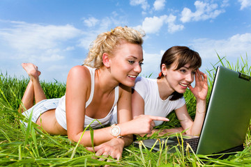 Two beautiful girls are laughing near laptop outdoors