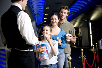 Family at the cinema handing tickets to the usher