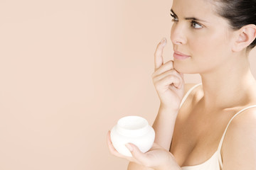 Woman applying moisturising cream to her face