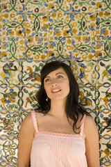 Young woman by decorated tiles, smiling, close-up