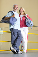 Senior couple with gym bags, leaning against railing, smiling, portrait
