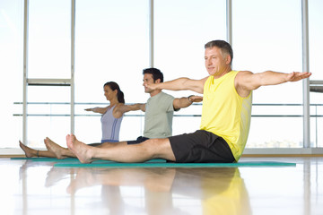 Two men and woman taking exercise class, low angle view