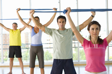 People taking exercise class, holding exercise bands above heads