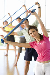 People taking exercise class with exercise bands, smiling