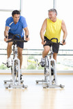 Two men on exercise bicycles in gym, smiling, low angle view