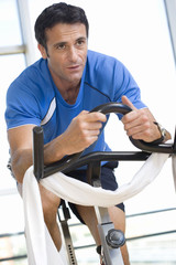 Man on exercise bicycle in gym, smiling, low angle view