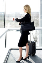 Businesswoman waiting at airport or station, checking her watch