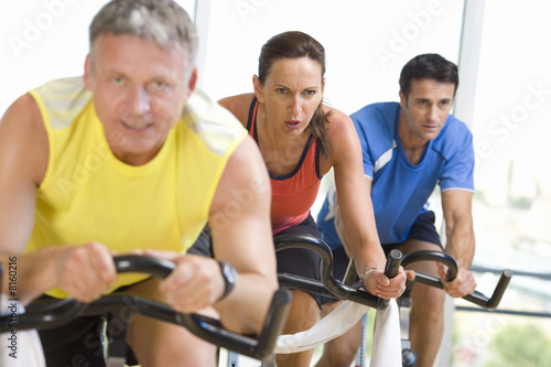 People on exercise bicycles in gym, smiling, portrait