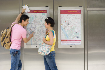 Couple looking at map on wall, smiling at each other, side veiw